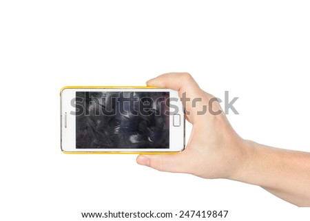 Hand holding white smartphone with fingerprint dirty screen