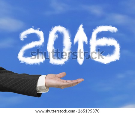 Hand holding white 2016 year arrow up sign shape clouds on blue sky background