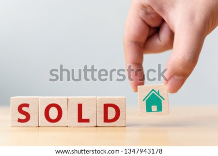 Hand holding wood cube block with icon house and word SOLD. Property investment and house mortgage financial concept