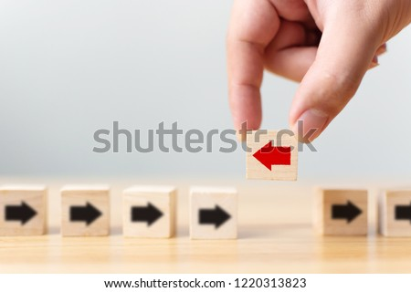Hand holding wooden block with red arrow facing the opposite direction black arrows, Unique, think different, individual and standing out from the crowd concept