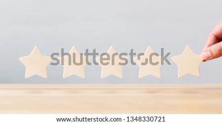 Hand holding wooden five star shape on table. The best excellent business services rating customer experience concept #1348330721