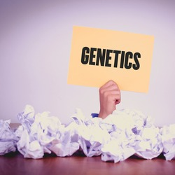 HAND HOLDING YELLOW PAPER WITH GENETICS CONCEPT