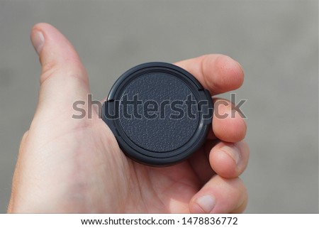 hand holds a black plastic lens cap on a gray background #1478836772