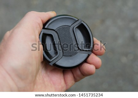 hand holds a black plastic lens cap on a gray background in the street #1451735234