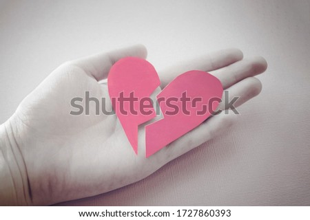 hand holds a broken heart. Grey and pink photo. Devorce and separation concept. Broken heart symbol. Paper heart. Relationship problems and lonliness. Two pieces of heart. Torn valentine card.