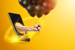 Hand holds a bunch of black balloons through a smartphone screen on a yellow background. Holiday concept, opening, copy space