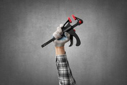 hand holds a construction tool clamp, on gray concrete wall background. Industrial concept