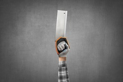 hand holds a construction tool - handsaw, on gray concrete wall background. Industrial concept