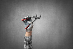 hand holds a construction tool pincer, on gray concrete wall background. Industrial concept