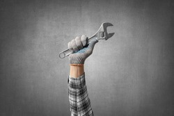 hand holds a construction tool steel adjustable spanner, on gray concrete wall background. Industrial concept