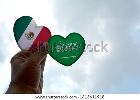 Hand holds a heart Shape Mexico and Saudi Arabia flag, love between two countries