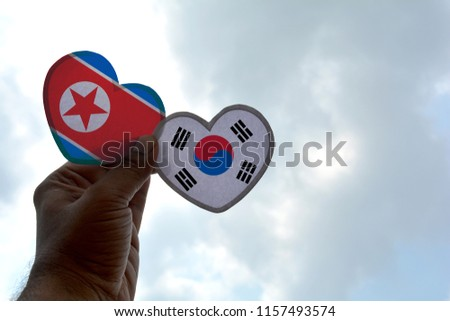 Hand holds a heart Shape North Korea and South Korea flag, love between two countries #1157493574