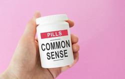 Hand holds a jar of pills, the inscription: COMMON SENSE