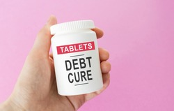 Hand holds a jar of pills, the inscription: DEBT CURE