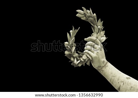 Hand holds a laurel wreath - bronze statue on black background - Success and fame concept image - image with copy space