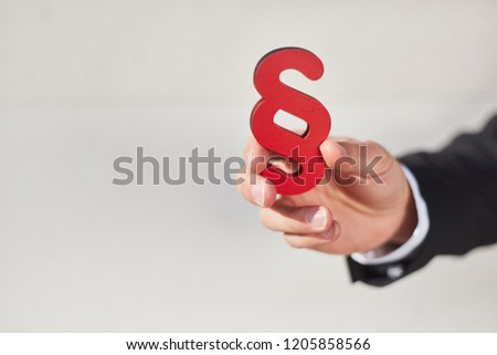 Hand holds a paragraph as a sign of justice and law and law