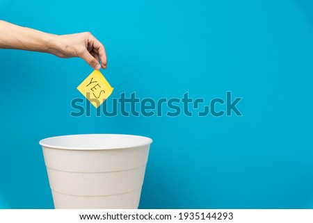 Hand holds a sticker with the inscription yes. White empty basket on blue background Stockfoto ©