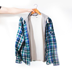 Hand holds a white t-shirt with plaid blue shirt on a hanger on a white background isolated