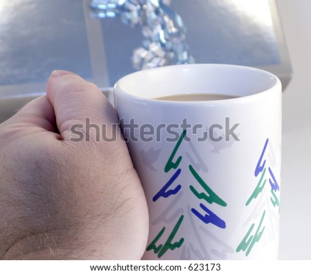 Hand holds Christmas mug with coffee in front of silver metallic wrapped gift package.