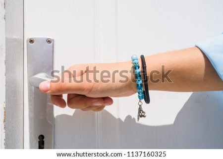 Hand Holds Doorknob On Wooden Front Door #1137160325