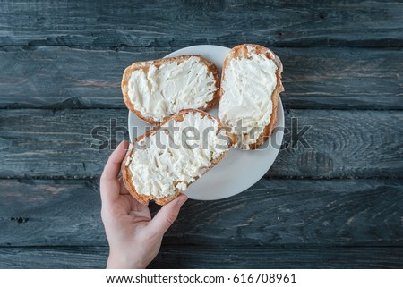 Hand holds homemade sandwich with cream-cheese over a black wooden table. Top view. Sandwiches on a white plate