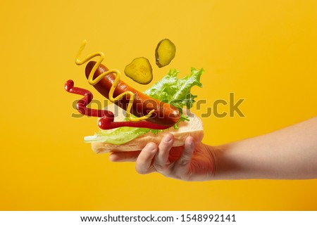 Hand holds hot dog in which sausage, salad, mustard, ketchup, pickle cucumbers are flying on a yellow background