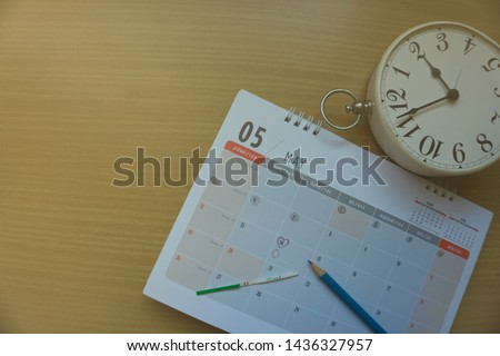 Hand holds LH test with two red marks with ovulation calendar plan  and white clock, Concept of fertility chart and cycle , trying to have baby and natural contraception, Reminder Ovulation in graph.