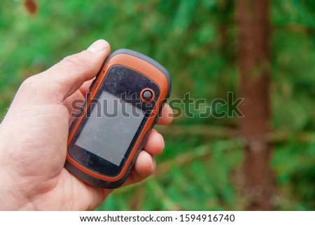 Hand holds  navigator. Orienteering using navigation systems.