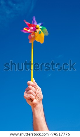 Hand holds rotating toy windmill over blue sky; slow shutter speed to catch motion