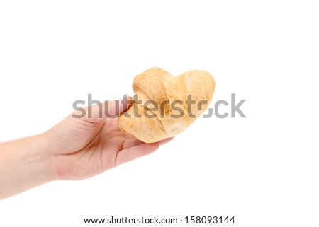 Hand holds striped fresh croissant. Isolated on a white background.