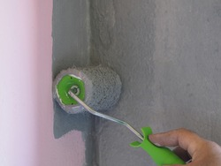 Hand holds the paint brush roller. Texture of a paint roller with light gray paint on a pink-gray wall background, closeup. Repair and painting of a concrete wall in pastel colors in a modern style