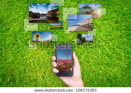 hand holds touch screen mobile phone streaming images on grass
