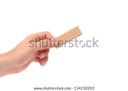 Hand holds wafer of chocolate. Isolated on a white background.