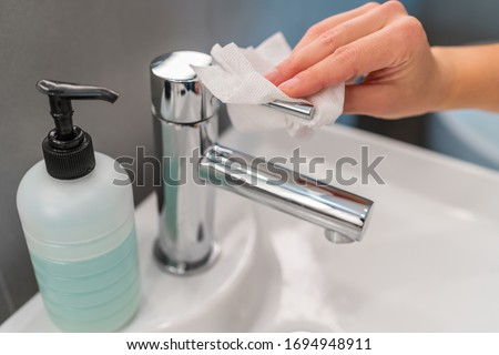 Hand hygiene hands washing step closing faucet tap with paper towel after drying hands for COVID-19 contamination prevention. Cleaning sanitizing wiping bathroom. Foto d'archivio ©