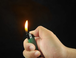 Hand Igniting Cigarette Lighter Isolated On Black Background