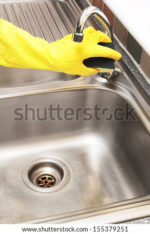 hand in a rubber glove cleaning a stainless steel sink with a sponge
