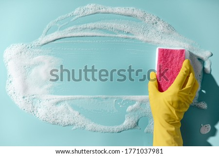 Hand in a yellow rubber glove holds a cleaning sponge and wipes a soapy foam on a blue background. Cleaning concept, cleaning service. Banner. Flat lay, top view