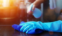 hand in blue rubber glove holding blue microfiber cleaning cloth and spray bottle with sterilizing solution make clean and disinfection for good hygiene