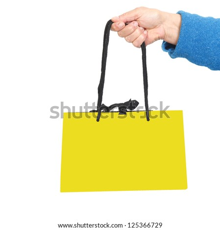 Hand in blue sweater holding bag with black cord