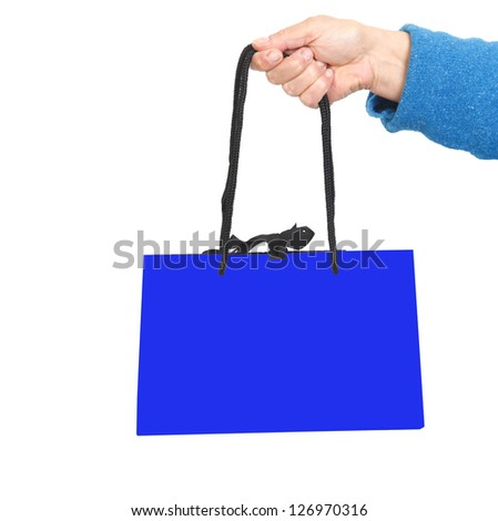 Hand in blue sweater holding dark blue bag with black cord