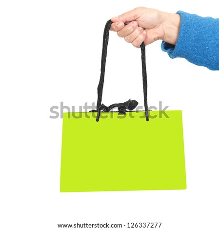 Hand in blue sweater holding green bag with black cord