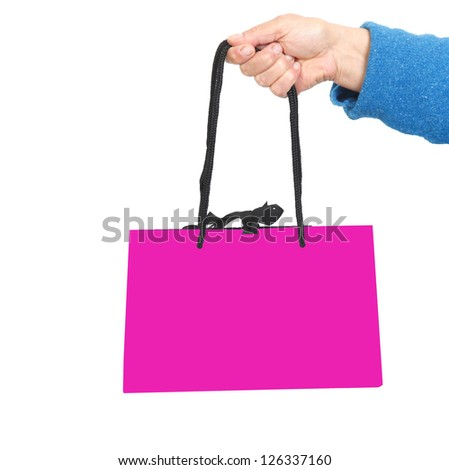 Hand in blue sweater holding pink bag with black cord