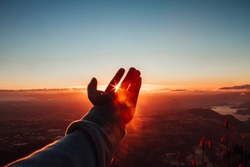 hand in front of the sunset with warm tones and a clear sky, while the sun passes through the fingers with rays of light