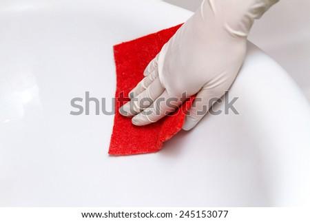 Hand in glove cleans washbasin red sponge