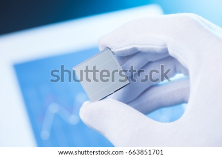 Hand in glove hold small solar panel, concept of new type solar cell research