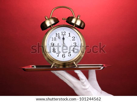 Hand in glove holding silver tray with alarm clock on red background