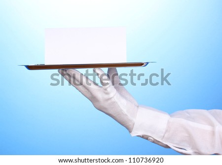 Hand in glove holding silver tray with blank card on blue background