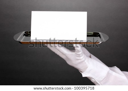Hand in glove holding silver tray with blank card on grey background