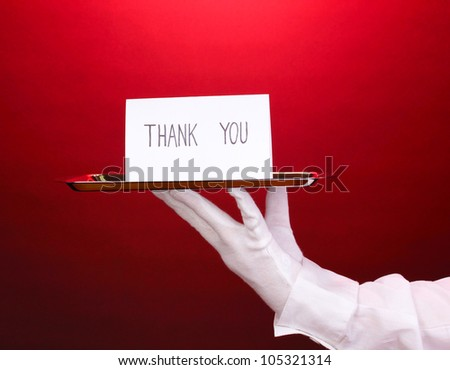 Hand in glove holding silver tray with card saying thank you on red background - stock photo