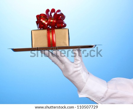 Hand in glove holding silver tray with giftbox on blue background